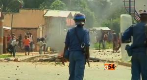 Lidé protestující proti třetí kandidatuře Pierra Nkurunziza pod dohledem policie, jež je údajně na prezidentově straně. Zdroj: youtube.com